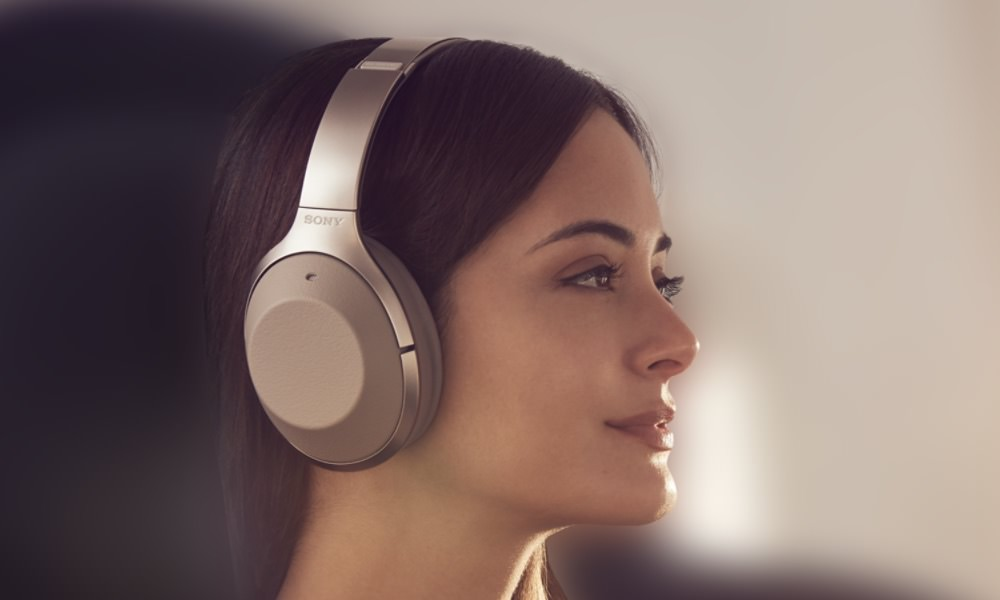 Sony WH-1000XM2 wireless noise-canceling headphones in gold on woman