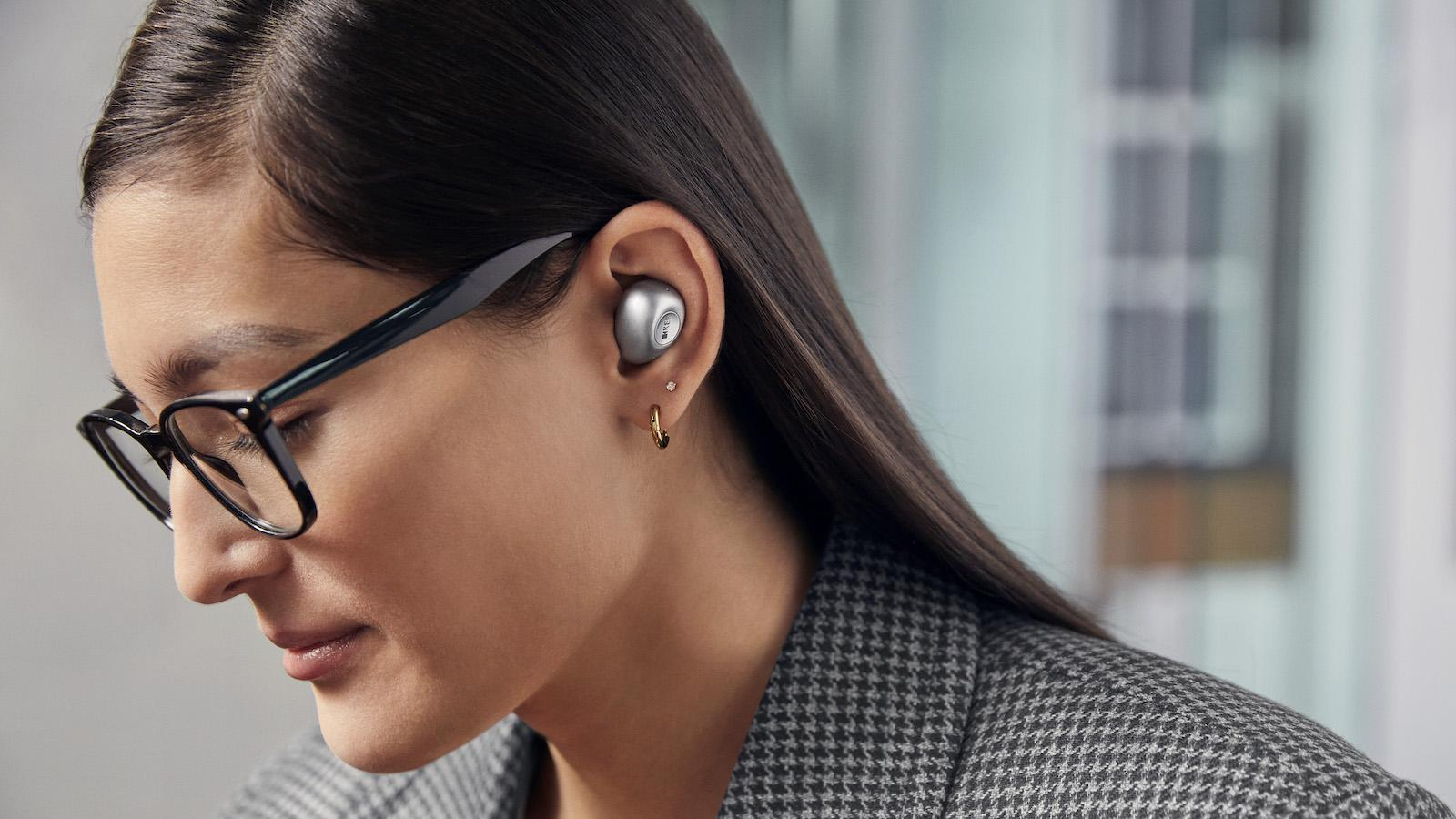 Woman wearing KEF Mu3 silver wireless earphones