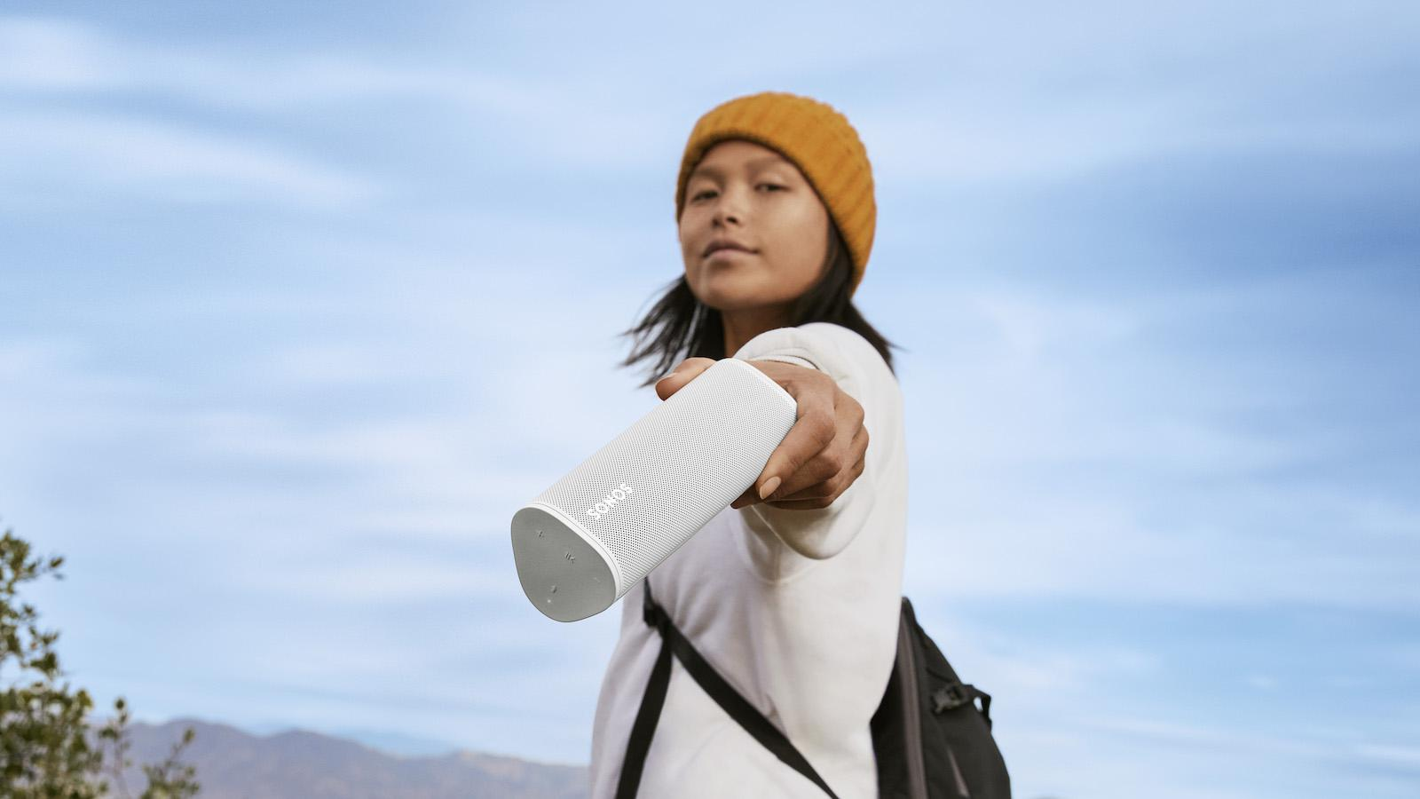 Woman Holding White Sonos Roam Portable Wireless Speaker