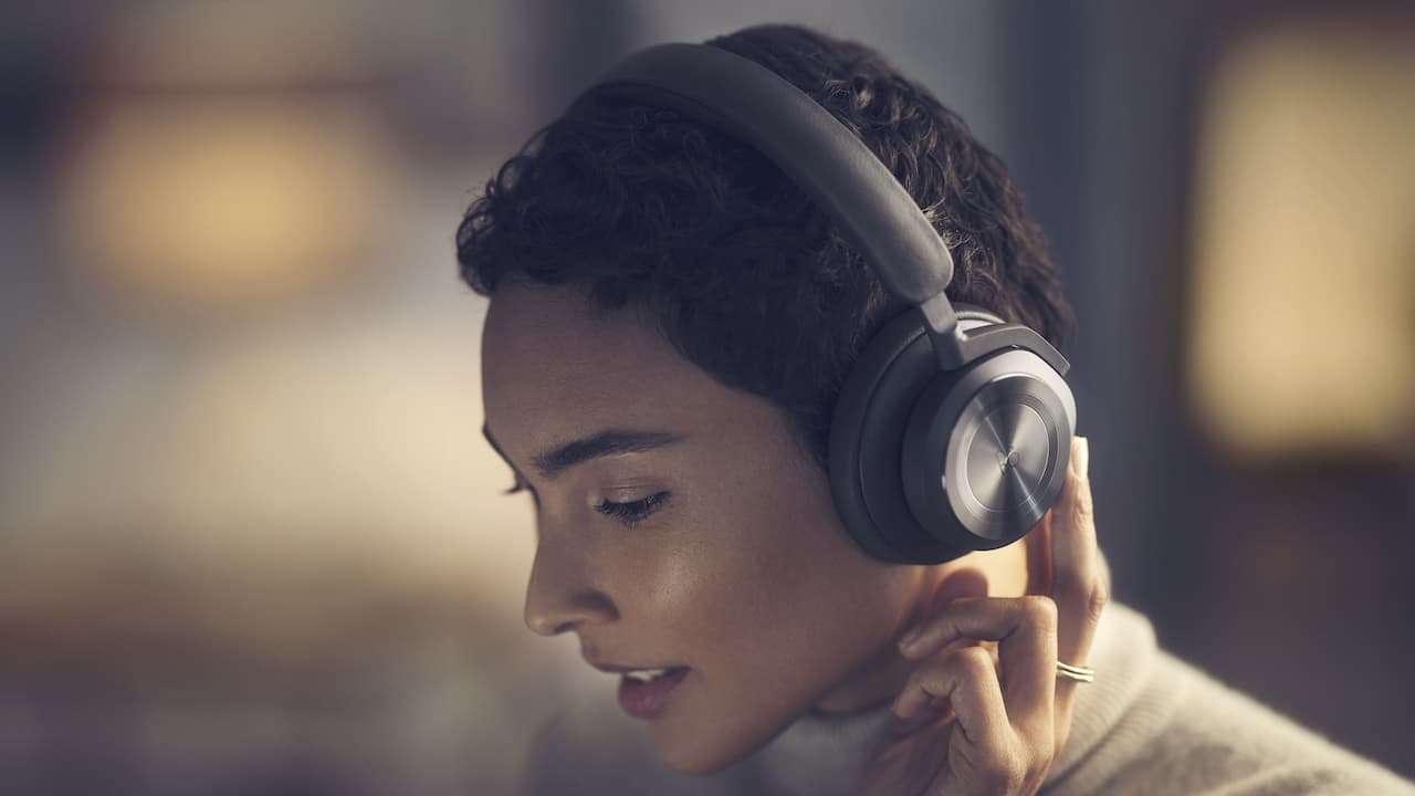 Woman adjusting Bang & Olufsen Beoplay HX Wireless Headphones