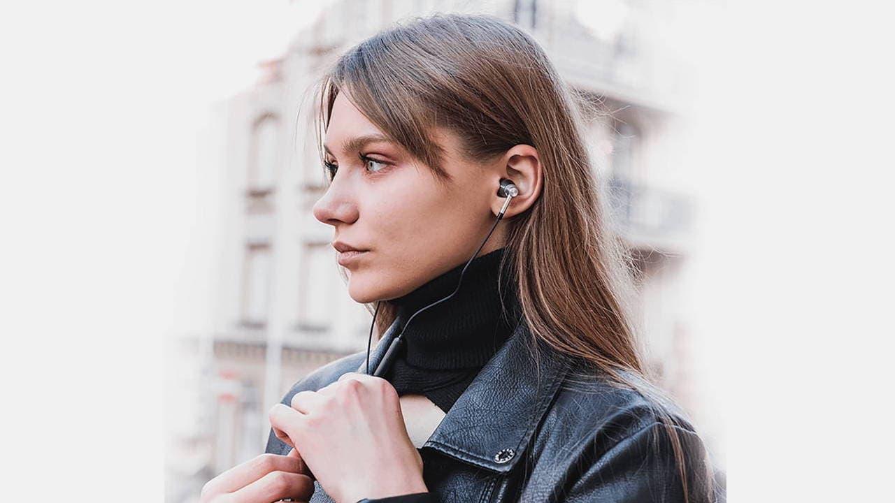 Woman wearing 1MORE Triple Driver THX Certified Wired Earphones