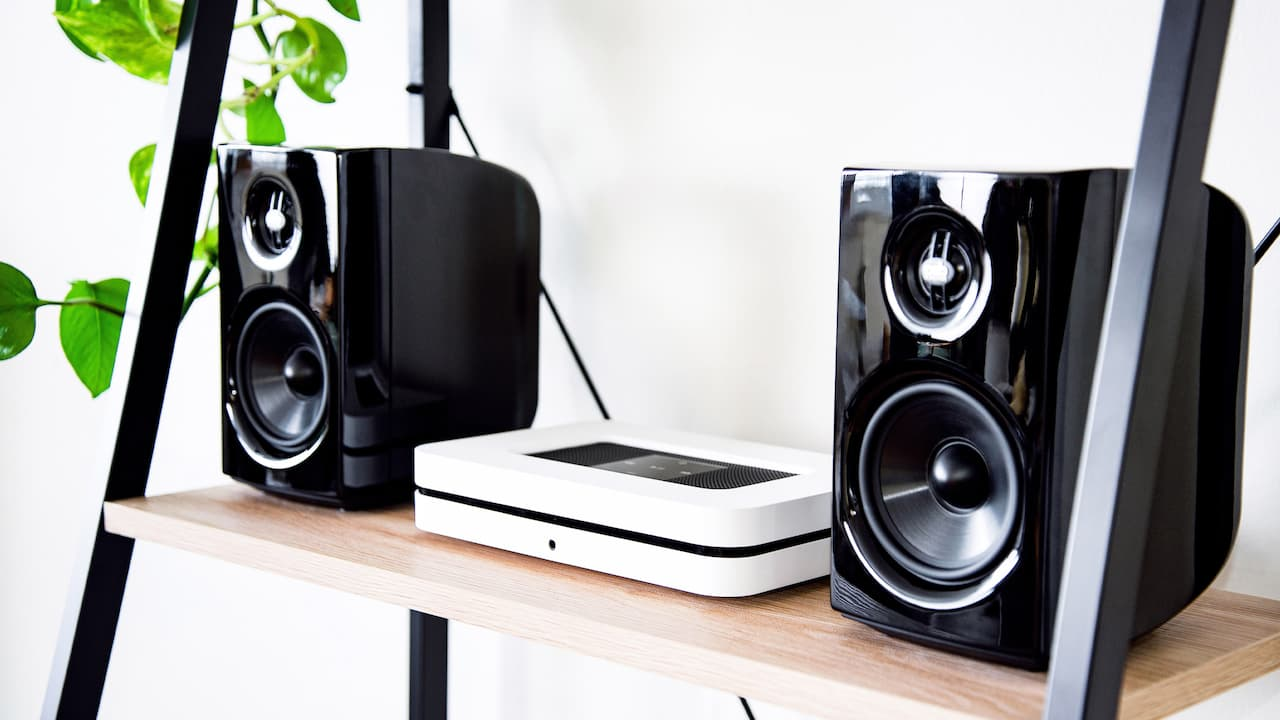 Bluesound Node 2i in White between to bookshelf speakers