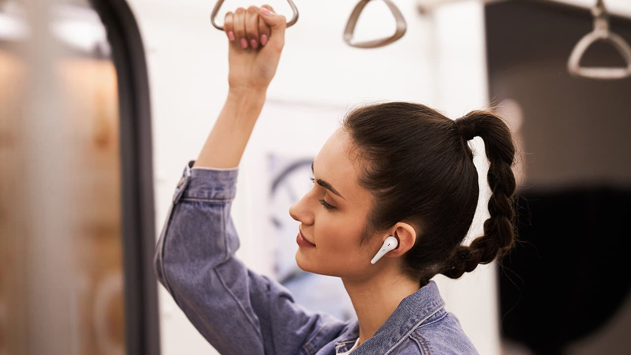 Woman in subway wearing 1More ComfoBuds Pro white wireless earphones