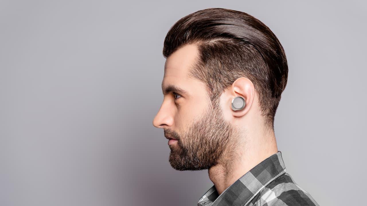 Man Profile wearing Cleer Ally Plus II Wireless Earphones Sand Color
