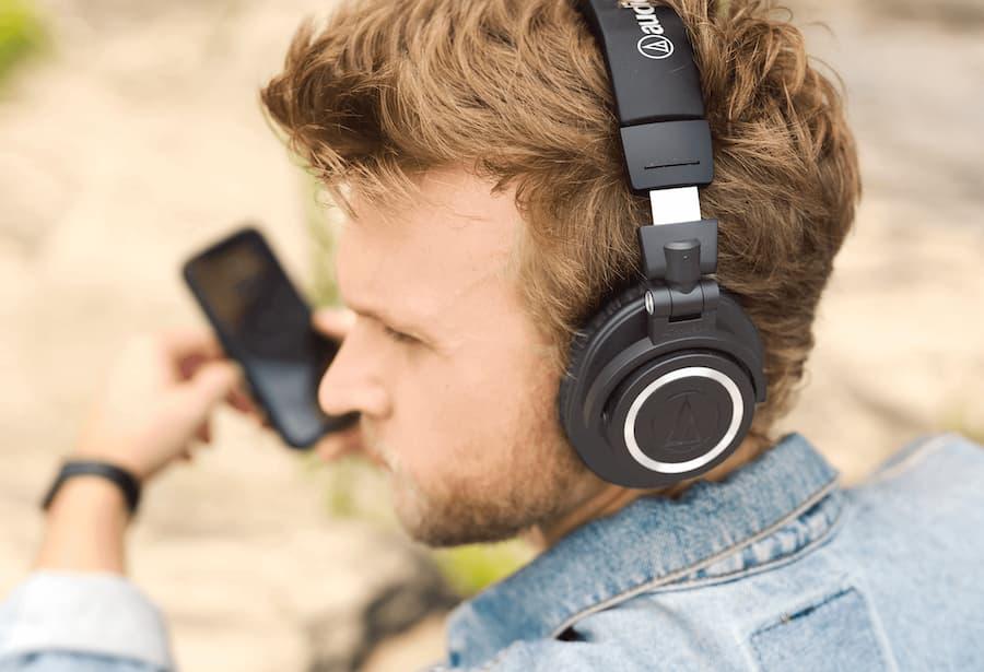 Man wearing Audio-Technica ATH-M50xBT2 Wireless Over-Ear Headphones